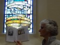 G15 Glennis Smith offers the stained glass William Guinness a look at the book  in Christ Church South Yarra